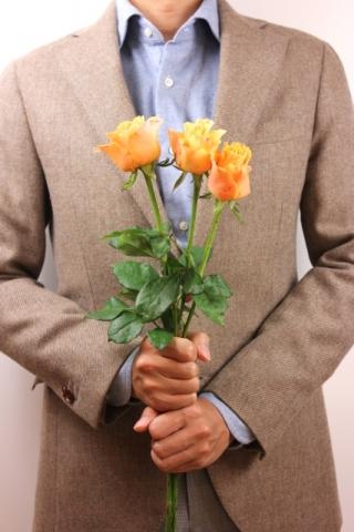 バラを手に持つ男性